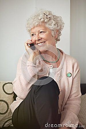 Lycklig hög kvinna på telefonen