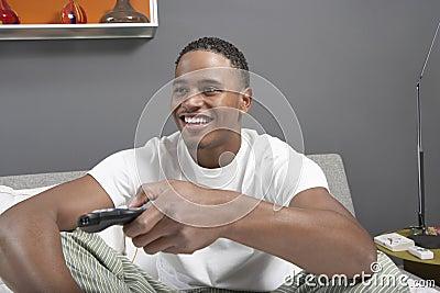 Lycklig hållande ögonen på TV för ung man