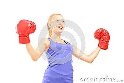 Lycklig kvinnlig idrottsman nen som bär röda boxninghandskar och gör en gest slumpen