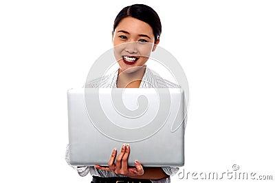 Lycklig kvinnlig yrkesmässig kvinna med bärbara datorn