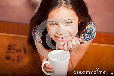 Lycklig liten flicka som dricker te