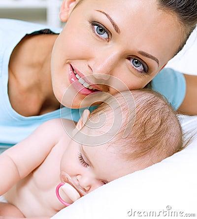 Lycklig moder nära nyfött sova barn