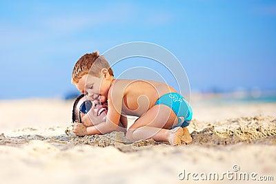 Lycklig unge som kramar faders huvud i sand på stranden
