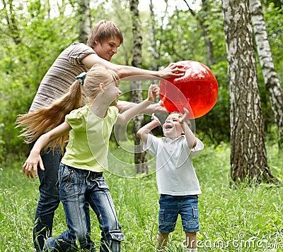 Lycklig utomhus- plaing för bollfamilj