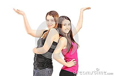 Lyckliga flickvänner som tillsammans står nära och gör en gest med