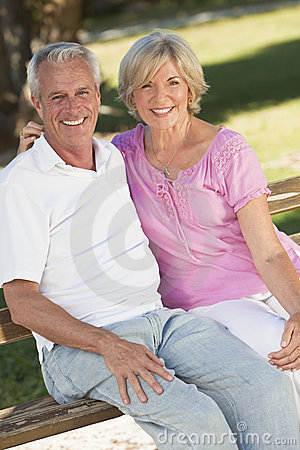 Lyckliga höga par som ler utanför i solsken
