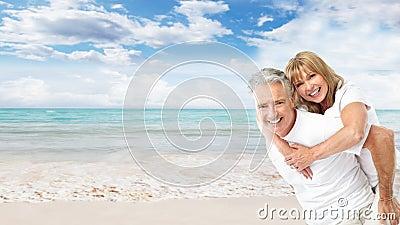 Lyckliga höga par på stranden.