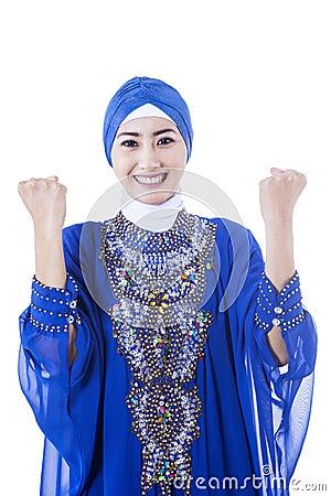 Lyckliga kvinnliga muslim i den isolerade blåttklänningen -
