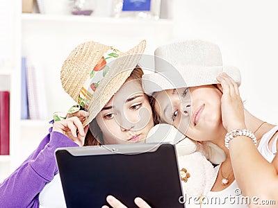Lyckliga roliga flickor ha tonårs- använda för touchpad