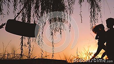 Lyckliga ungar som har utomhus- gyckel Pys och flicka som spelar med gunga nära sjön under härlig solnedgång lager videofilmer