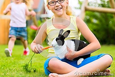 Lyckligt barn med kaninhusdjuret hemma i trädgård