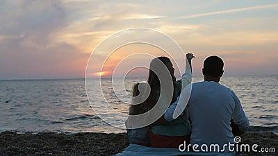 Lyckligt familjsammanträde i solnedgången nära havet in stock video