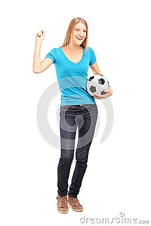 Lyckligt kvinnligt fläktar innehav en fotboll och göra en gest