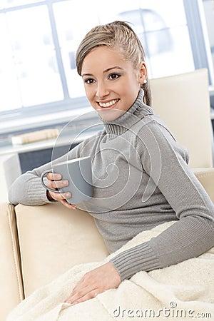 Lyckligt kvinnligt med tea och filten