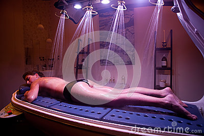 Lying relaxed woman during spa treatment. Color Therapy.