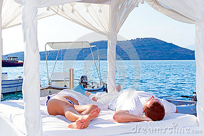 Lying on white bed at the sea