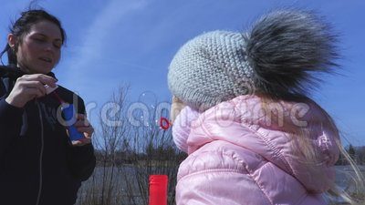 A mãe aprende sua filha pequena fundir bolhas de sabão filme