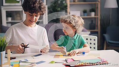 Mãe e filho que fazem as colagens que cortam o papel e que colam com colagem na tabela vídeos de arquivo