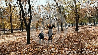 A mãe e o filho recolhem e trow acima das folhas amarelas em um parque do outono filme