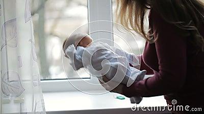 A mãe está perto da janela e dos berços recém-nascidos video estoque
