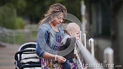 Mãe feliz nova com o bebê pequeno na ponte no parque Aprecie a beleza da natureza vídeos de arquivo