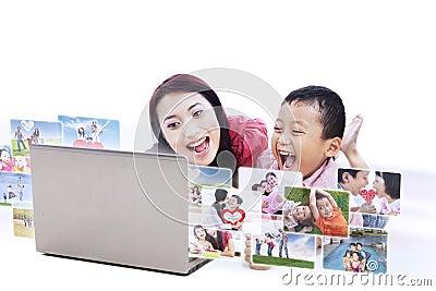 Mãe feliz que olha as fotos de família digitais - isoladas