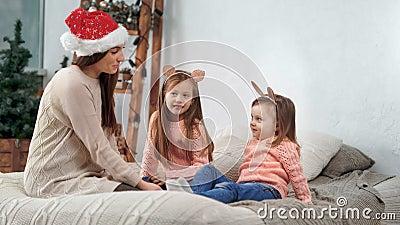Mãe jovem no chapéu de Papai Noel brincando com duas filhas bonitinhas usando ouvidos festivos engraçados vídeos de arquivo
