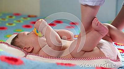A m?e muda o tecido para seu beb? rec?m-nascido no ber??rio Cuidado rec?m-nascido, mudan?a do tecido, beb? saud?vel video estoque