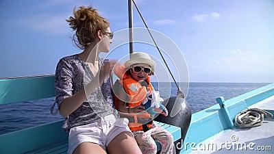 A mãe nova e sua filha pequena estão navegando em um barco de mar Movimento lento vídeos de arquivo