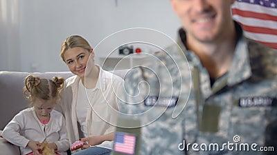 Mãe nova que joga com a filha, olhando o marido militar, defesa da família video estoque