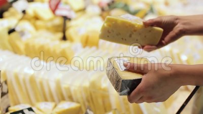 Mão do comprador com uma parte de queijo na loja video estoque