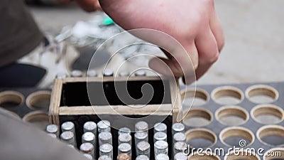 A mão do homem põe os pinos metálicos cilíndricos na caixa de madeira com furos redondos filme
