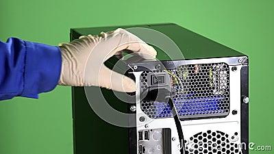A mão do técnico nas luvas desconecta no cabo bonde ao botão do PC e da imprensa video estoque