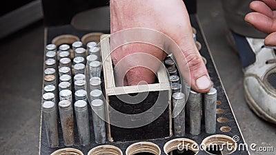 A mão do trabalhador do homem põe os pinos metálicos cilíndricos na caixa de madeira com furos redondos video estoque