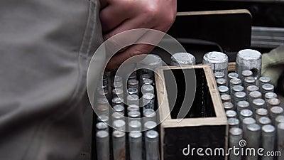 A mão do trabalhador põe os pinos metálicos cilíndricos na caixa de madeira com furos redondos video estoque