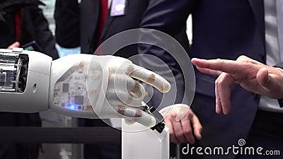 Mão e robô humanos como um símbolo da conexão entre os povos e a inteligência artificial que executam o metal pesado filme