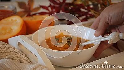 A mão feminina colocou tigela com sopa de abóbora na bandeja branca com folhas de outono e abóbora sobre o fundo vídeos de arquivo