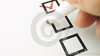 Mão masculina que põe a lista de verificação da caixa de seleção da marca video estoque
