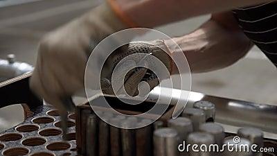 A mão nas luvas toma os pinos metálicos cilíndricos da caixa de madeira com furos redondos video estoque
