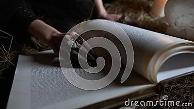 Mão negra da bruxa gasta no texto do livro de feitiços imagem de Halloween video estoque