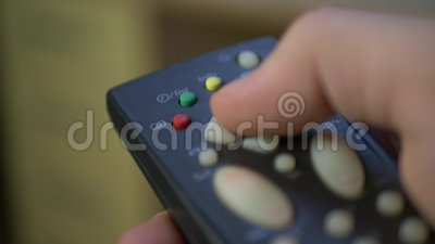 Mão que guarda o controlador remoto preto e as teclas da tevê filme