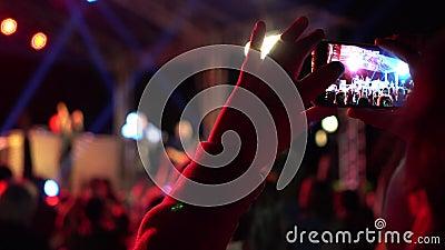 Mãos da menina que fazem o vídeo do concerto do festival do verão com telefone celular Multidão que comemora o evento do partido  vídeos de arquivo