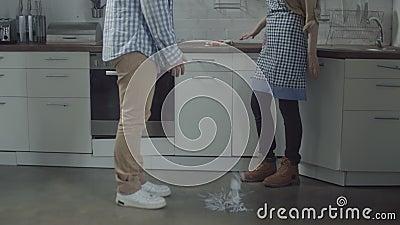 Mãos fêmeas que despedaçam a placa no assoalho da cozinha filme