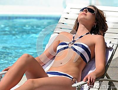 Mädchen, das durch das Pool ein Sonnenbad nimmt