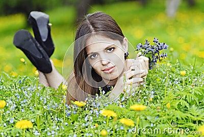 Mädchen, das in einem Gras mit einem Blumenstrauß liegt