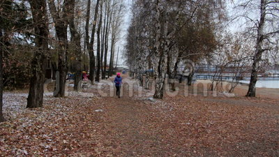 Mädchen, das in Herbstpark während des kalten bewölkten Tages läuft Frau, die draußen trainiert
