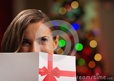 Mädchen, das hinter Weihnachtspostkarte sich versteckt
