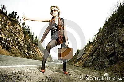 Mädchen, das mit Koffer trampt