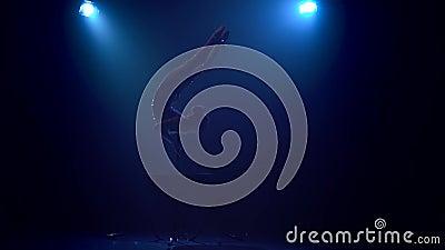 Mädchen führt am Stadium mit verschiedenen akrobatischen Bremsungen in einem glänzenden Kostüm durch Rauchblauhintergrund Langsam stock video footage