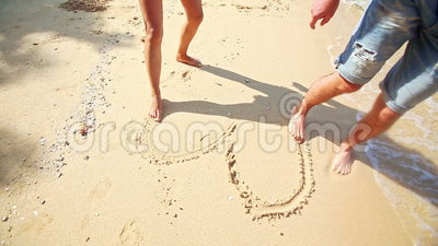 Mädchen Guy Feet Barefoot Draw Heart auf Sand-Strand am Wellen-Rand stock video